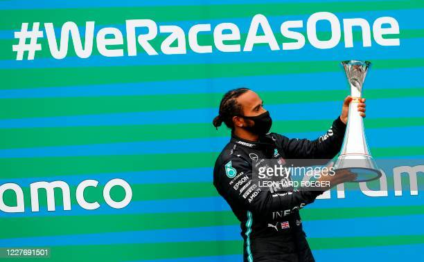 Mercedes' British driver Lewis Hamilton celebrates with the trophy on the podium of the Formula One Hungarian Grand Prix race at the Hungaroring...