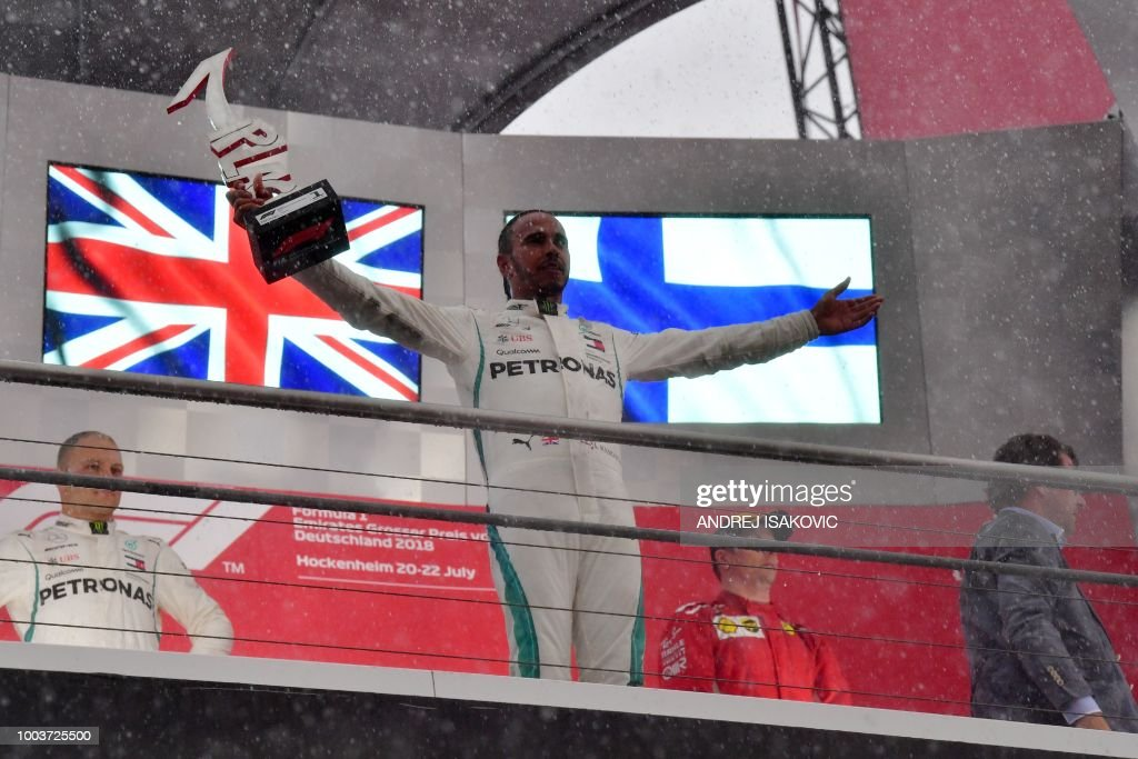 TOPSHOT - Mercedes' British driver Lewis Hamilton celebrates with the trophy after winning the German Formula One Grand Prix at the Hockenheim racing circuit on July 22, 2018 in Hockenheim, southern Germany.
