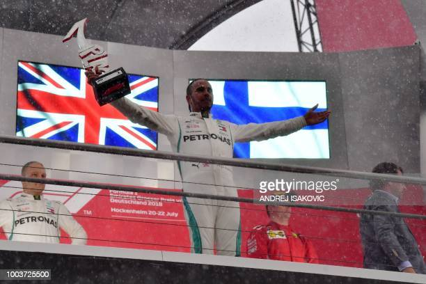 TOPSHOT Mercedes' British driver Lewis Hamilton celebrates with the trophy after winning the German Formula One Grand Prix at the Hockenheim racing...