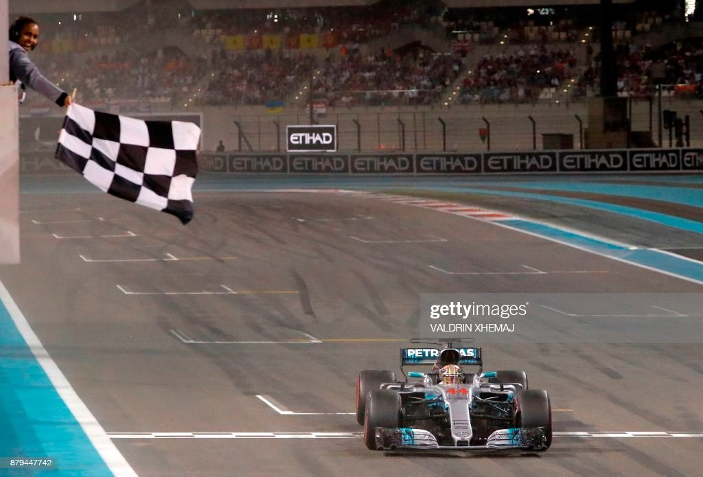 TOPSHOT - Mercedes' British driver Lewis Hamilton crosses the finish line during the Abu Dhabi Formula One Grand Prix at the Yas Marina circuit on November 26, 2017. Finland's Valtteri Bottas won the season-ending Abu Dhabi Grand Prix on Sunday, finishing ahead of world champion Lewis Hamilton with Sebastian Vettel taking third. /