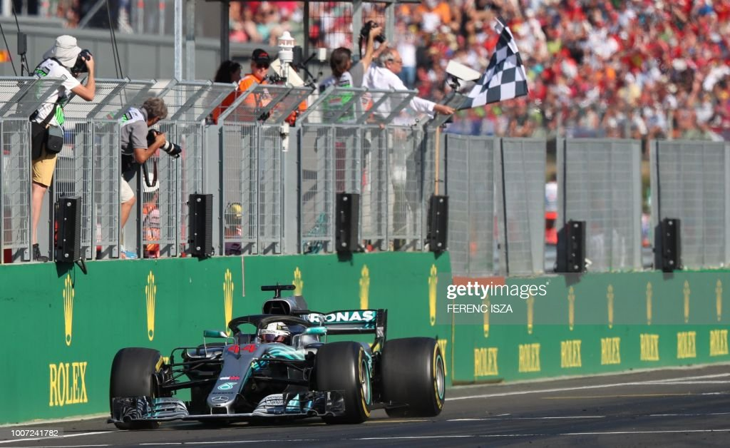 TOPSHOT - Mercedes' British driver Lewis Hamilton crosses the finish line to win the Formula One Hungarian Grand Prix at the Hungaroring circuit in Mogyorod near Budapest, Hungary, on July 29, 2018.