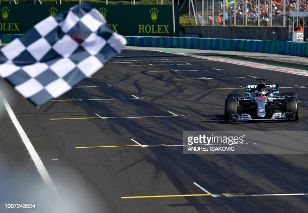 TOPSHOT Mercedes' British driver Lewis Hamilton crosses the finish line to win the Formula One Hungarian Grand Prix at the Hungaroring circuit in...