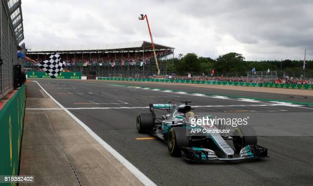 Mercedes' British driver Lewis Hamilton crosses the finish line to win for the fourth time the British Formula One Grand Prix at the Silverstone...