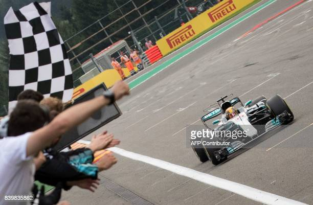 Mercedes' British driver Lewis Hamilton crosses the finish line to win the Belgian Formula One Grand Prix at the SpaFrancorchamps circuit in Spa on...