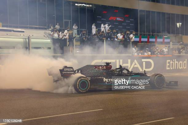 Mercedes' British driver Lewis Hamilton does doghnuts after the Abu Dhabi Formula One Grand Prix at the Yas Marina Circuit in the Emirati city of Abu...