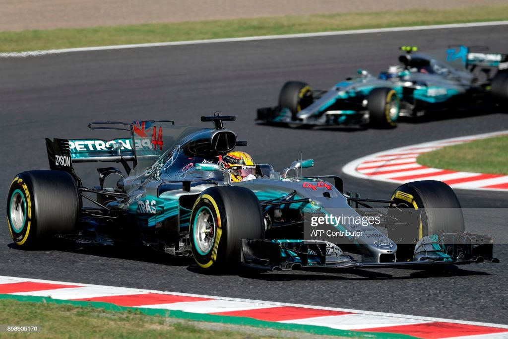Mercedes' British driver Lewis Hamilton (bottom) drives during the Formula One Japanese Grand Prix at Suzuka on October 8, 2017. / AFP PHOTO / Kiyoshi OTA
