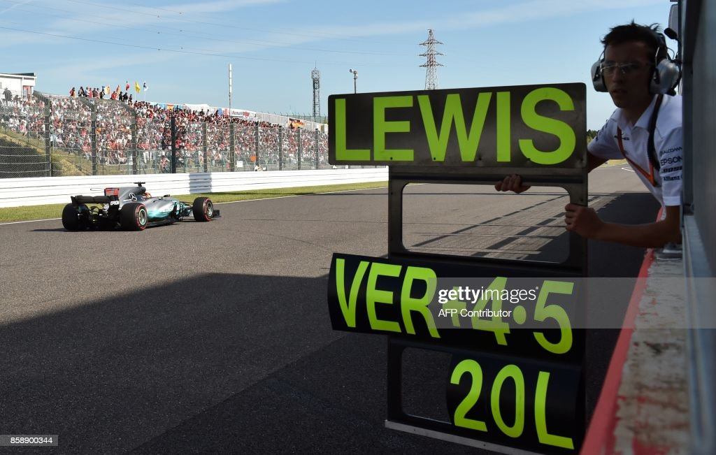 TOPSHOT - Mercedes' British driver Lewis Hamilton drives past a sign board during the Formula One Japanese Grand Prix at Suzuka on October 8, 2017. /