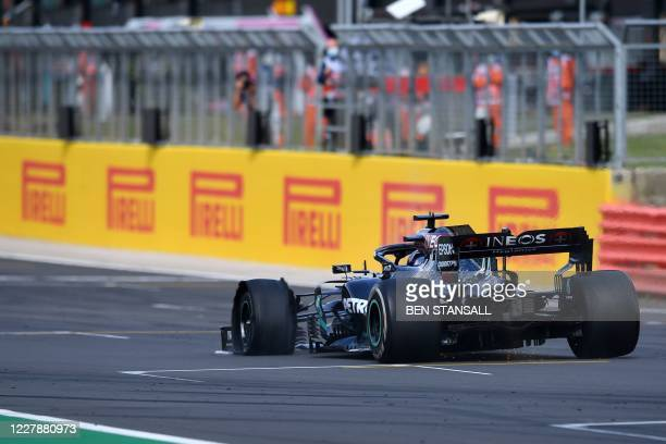 Mercedes' British driver Lewis Hamilton drives with a puncture before winning the Formula One British Grand Prix at the Silverstone motor racing...