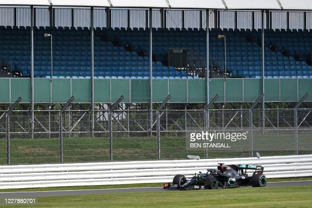 Mercedes' British driver Lewis Hamilton drives with a puncture past empty stands as he returns to the pits after winning the Formula One British...
