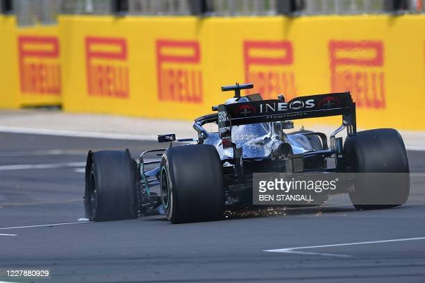 Mercedes' British driver Lewis Hamilton drives with a puncture towards the finish line to win the Formula One British Grand Prix at the Silverstone...