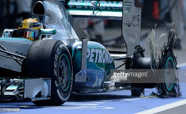 Mercedes' British driver Lewis Hamilton enters the pit with a puncture at the Silverstone circuit in Silverstone on June 30 2013 during the British...