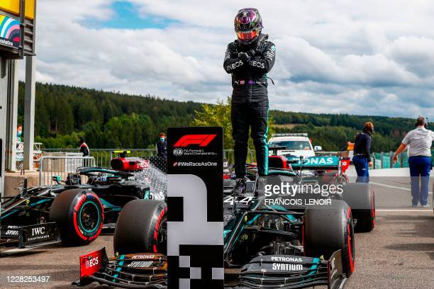 Mercedes' British driver Lewis Hamilton gestures in homage to late US actor Chadwick Boseman, as he stands on his car after securing his 93rd pole...