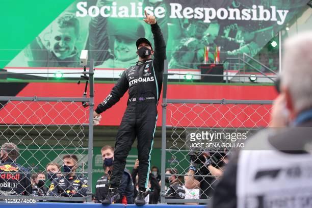 Mercedes' British driver Lewis Hamilton gestures to the spectators after winning the Portuguese Formula One Grand Prix at the Autodromo Internacional...