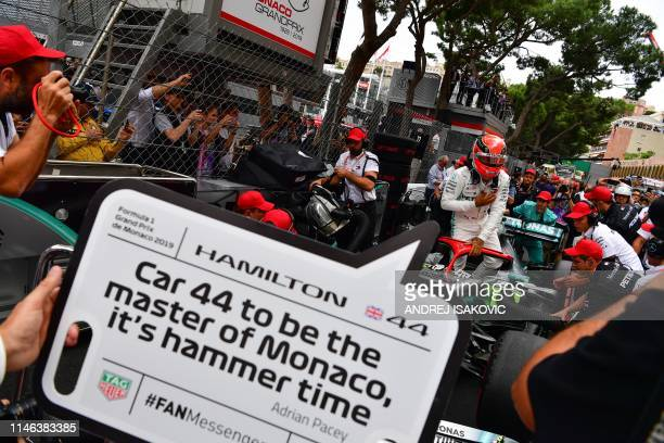 Mercedes' British driver Lewis Hamilton gets into his car as a grid boy holds placard with a twitter quote reading 'Car 44 to be the master of Monaco...