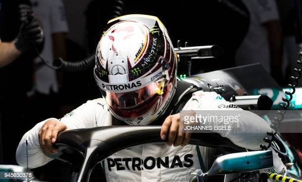 TOPSHOT Mercedes' British driver Lewis Hamilton gets into his car during a practice session for the Formula One Chinese Grand Prix in Shanghai on...