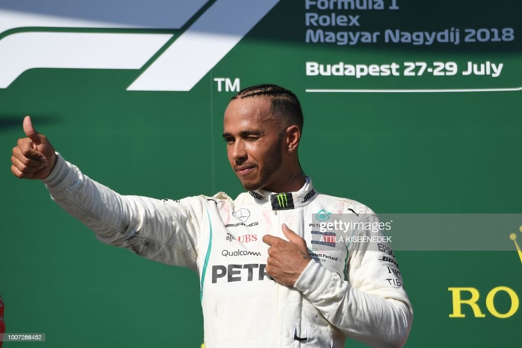 Mercedes' British driver Lewis Hamilton gives the thumb up as he celebrates on the podium after winning the Formula One Hungarian Grand Prix at the Hungaroring circuit in Mogyorod near Budapest, Hungary, on July 29, 2018.