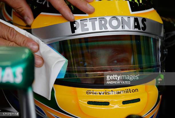 Mercedes' British driver Lewis Hamilton has his visor cleaned in the pits during the second practice session at the Silverstone circuit in...