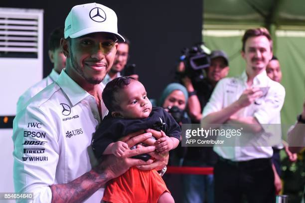 Mercedes' British driver Lewis Hamilton holds an unidentified infant during a meet the fans session in Kuala Lumpur on September 27 ahead of the...