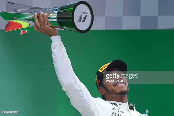 Mercedes' British driver Lewis Hamilton holds his trophy as he celebrates on the podium after winning the Formula One Chinese Grand Prix in Shanghai...