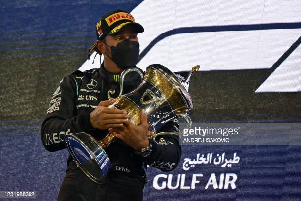 Mercedes' British driver Lewis Hamilton holds the winner's trophy on the podium after the Bahrain Formula One Grand Prix at the Bahrain International...