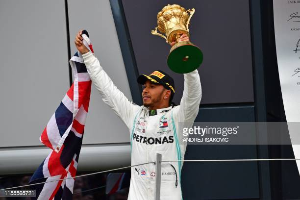 Mercedes' British driver Lewis Hamilton holds up the trophy on the podium as he celebrates victory in the British Formula One Grand Prix at the...