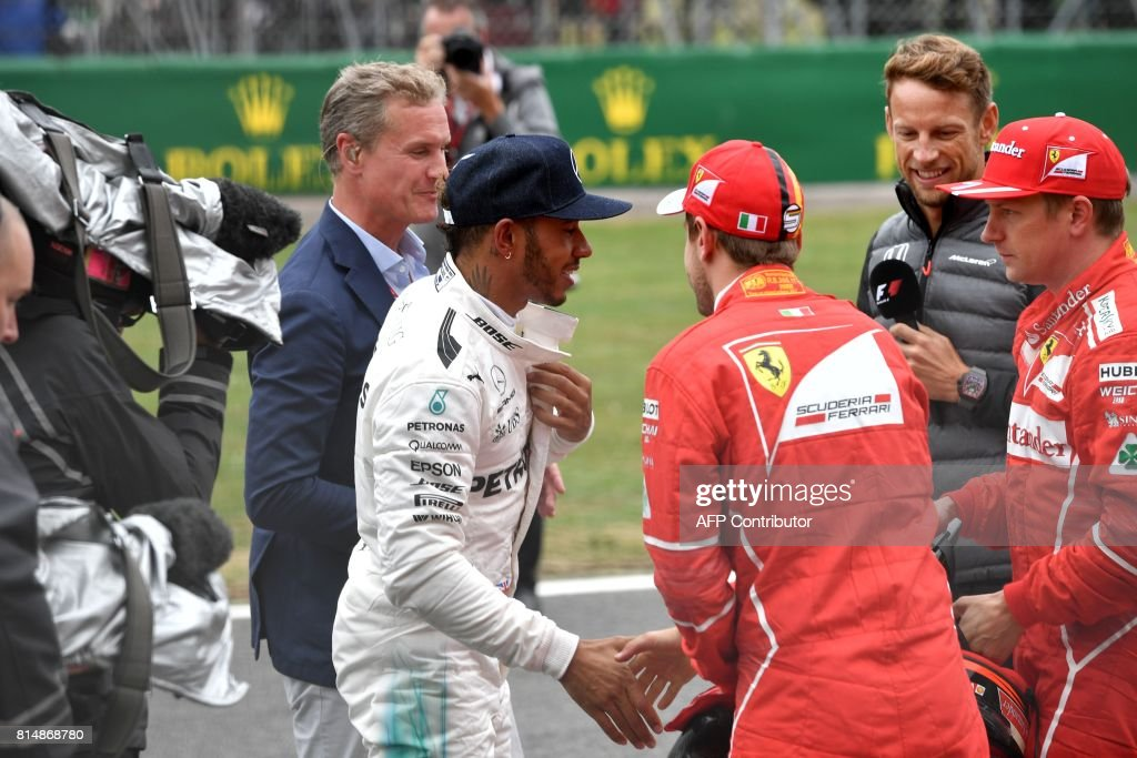 Mercedes' British driver Lewis Hamilton (2L) is congratulated after winning the pole position by second placed Ferrari's Finnish driver Kimi Raikkonen (R) and third placed Ferrari's German driver Sebastian Vettel as they stand next to former Formula One driver David Coulthard (L) and British driver Jenson Button (2R) after the qualifying session at the Silverstone motor racing circuit in Silverstone, central England on July 15, 2017 ahead of the British Formula One Grand Prix. / AFP PHOTO / Andrej ISAKOVIC