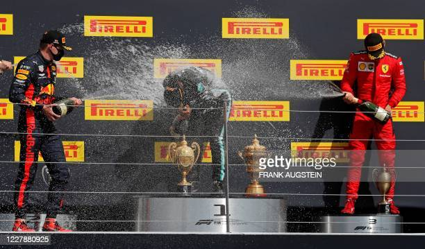 Mercedes' British driver Lewis Hamilton is sprayed with champagne by second-placed Red Bull's Dutch driver Max Verstappen and third-placed Ferrari's...