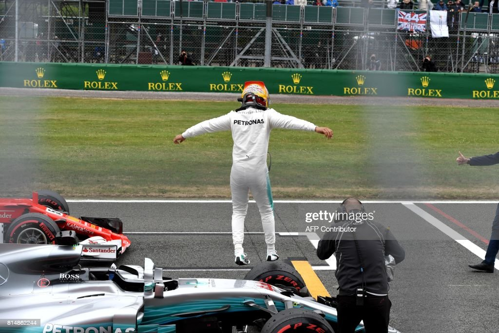 Mercedes' British driver Lewis Hamilton jumps off his car after winning the pole position during the qualifying session at the Silverstone motor racing circuit in Silverstone, central England on July 15, 2017 ahead of the British Formula One Grand Prix. / AFP PHOTO / Andrej ISAKOVIC