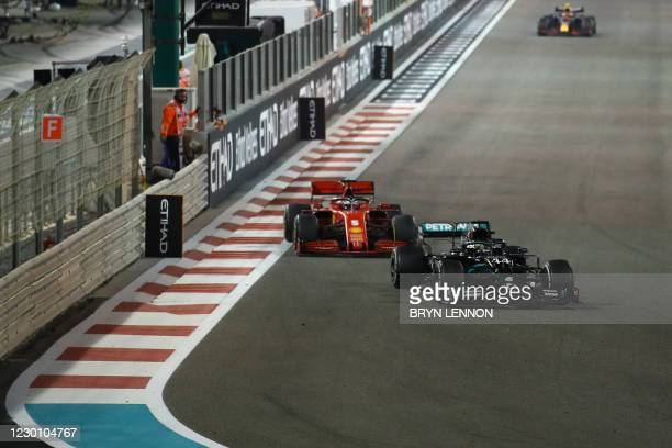 Mercedes' British driver Lewis Hamilton laps Ferrari's German driver Sebastian Vettel during the Abu Dhabi Formula One Grand Prix at the Yas Marina...