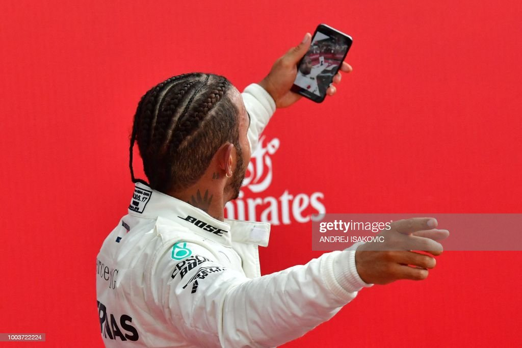TOPSHOT - Mercedes' British driver Lewis Hamilton makes a selfie with his mobile phone after winning the German Formula One Grand Prix at the Hockenheim racing circuit on July 22, 2018 in Hockenheim, southern Germany.