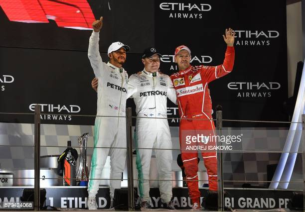Mercedes' British driver Lewis Hamilton Mercedes' Finnish driver Valtteri Bottas and Ferrari's German driver Sebastian Vettel celebrate on the podium...