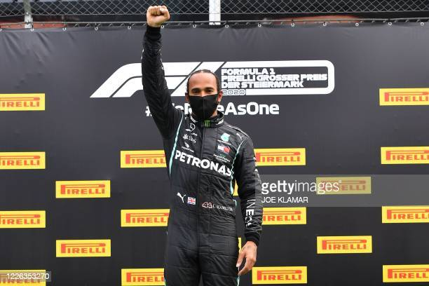 Mercedes' British driver Lewis Hamilton raises a fist in support of the Black Lives matter movement on the podium after winning the Formula One...
