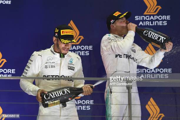 Mercedes' British driver Lewis Hamilton sprays champagne beside thirdplaced Mercedes' Finnish driver Valtteri Bottas after winning the Formula One...