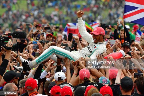Mercedes' British driver Lewis Hamilton surfs on a wave of supporters as he celebrates after victory in the British Formula One Grand Prix at the...