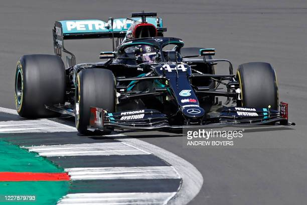 Mercedes' British driver Lewis Hamilton takes a corner on the opening lap of the Formula One British Grand Prix at the Silverstone motor racing...