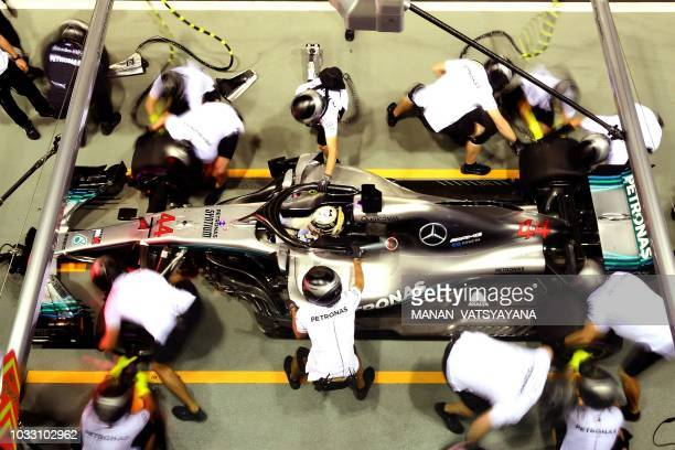 TOPSHOT Mercedes' British driver Lewis Hamilton takes a pit stop during the second practice session at the Marina Bay Street Circuit ahead of the...