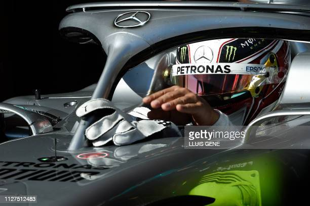 Mercedes' British driver Lewis Hamilton takes off his gloves as he takes part in the tests for the new Formula One Grand Prix season at the Circuit...