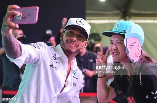 TOPSHOT Mercedes' British driver Lewis Hamilton takes pictures during a meet the fans session in Kuala Lumpur on September 27 ahead of the Malaysia...