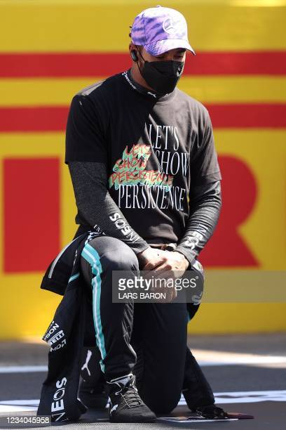 Mercedes' British driver Lewis Hamilton takes the knee before the Formula One British Grand Prix motor race at Silverstone motor racing circuit in...