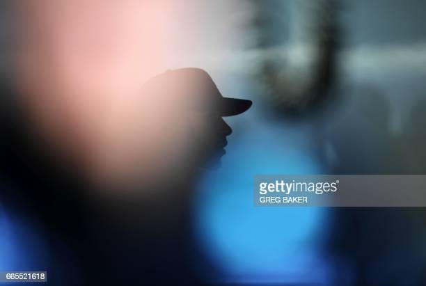 TOPSHOT Mercedes' British driver Lewis Hamilton walks through his pit garage during the practice session ahead of the Formula One Chinese Grand Prix...