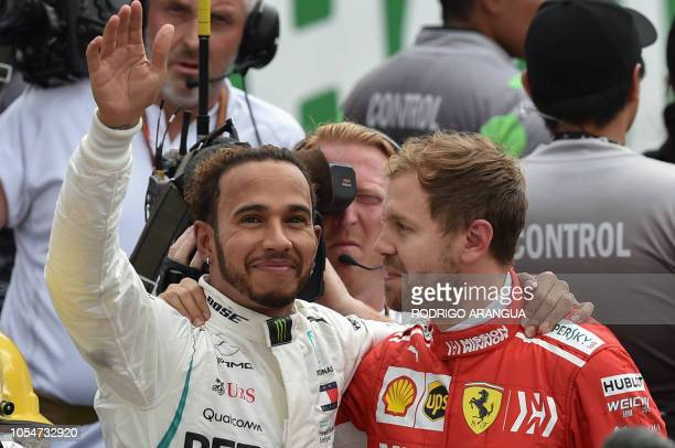 TOPSHOT Mercedes' British driver Lewis Hamilton waves at the crowd as he hugs Ferrari's German driver Sebastian Vettel after winning his fifth...