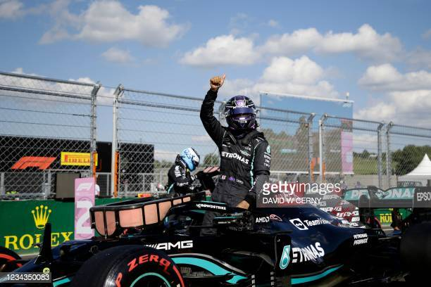 Mercedes' British driver Lewis Hamilton waves from his car as he celebrates winning the pole position after the qualifying session at the Hungaroring...
