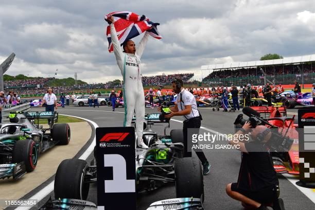 TOPSHOT Mercedes' British driver Lewis Hamilton waves the Union flag as he celebrates in parc ferme after victory in the British Formula One Grand...