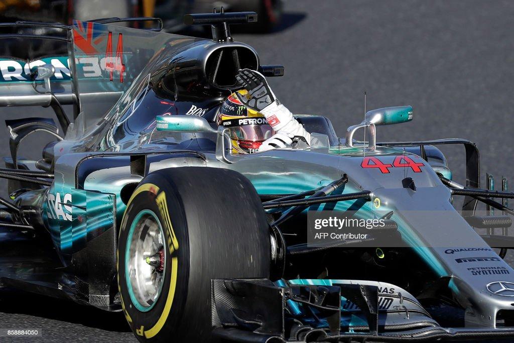 TOPSHOT - Mercedes' British driver Lewis Hamilton waves to fans as he celebrates after winning the Formula One Japanese Grand Prix at Suzuka on October 8, 2017. / AFP PHOTO / Kiyoshi OTA