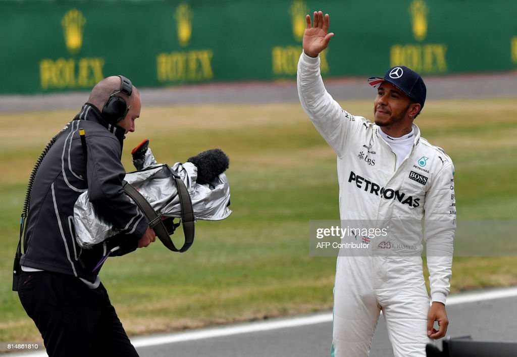 Mercedes' British driver Lewis Hamilton (R) waves to supporters after winning the pole position during the qualifying session at the Silverstone motor racing circuit in Silverstone, central England on July 15, 2017 ahead of the British Formula One Grand Prix. / AFP PHOTO / Ben STANSALL