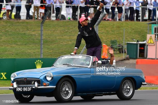 Mercedes' British driver Lewis Hamilton waves to the crowd from a vintage MGC Roadster 1968 driven by his father Anthony on a parade lap ahead of the...