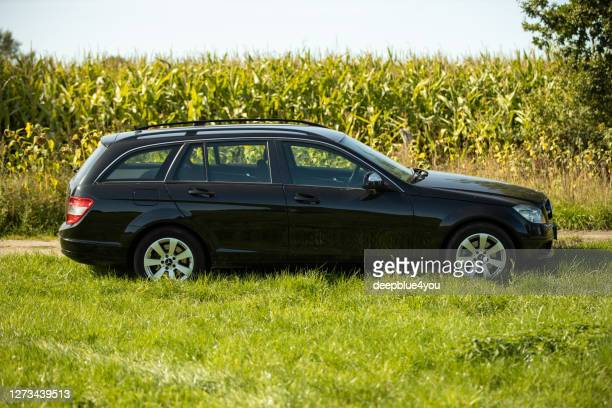 mercedes c class t model,  side view,  parked in the country on a meadow - straßenverkehr stock pictures, royalty-free photos & images