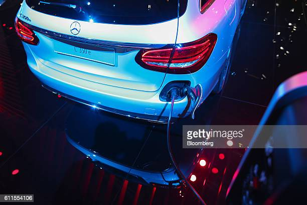 Mercedes C350e electric automobile, manufactured by Mercedes-Benz AG, sits connected to a charging plug during the second press day of the Paris...