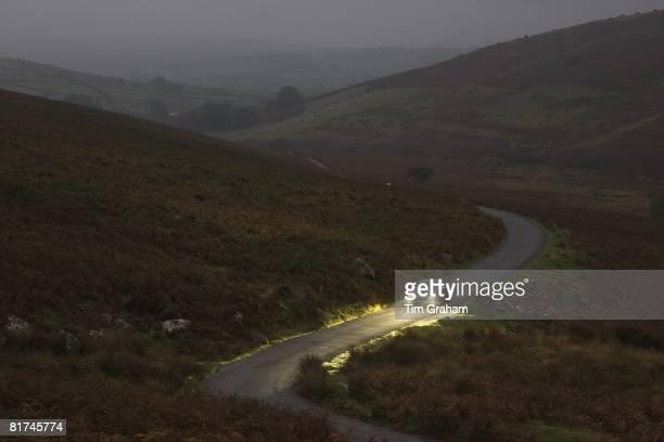 Mercedes car drives along a country road at night Dartmoor Devon United Kingdom