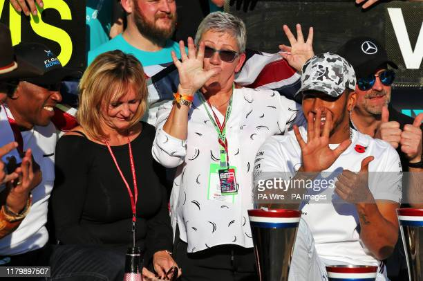 Mercedes driver Lewis Hamilton celebrates winning his sixth world championship with his mum Carmen Larbalestier and his dad Anthony after the United...